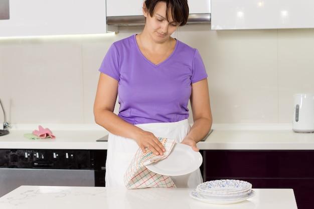 食後に夕食の皿を乾かす主婦
