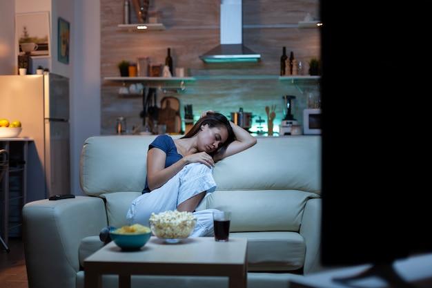 テレビの前のソファのリビングルームで眠りに落ちる主婦。居間の快適なソファで寝て、夜にテレビを見ながら目を閉じて、パジャマ姿で疲れ果てた孤独な眠そうな女性