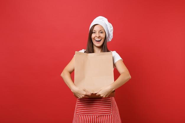 Домохозяйка женщина-шеф-повар пекарь в полосатом фартуке, футболке, шляпе шеф-повара, изолированной на красном фоне стены женщина держит в руке коричневый чистый пустой пустой ремесленный бумажный мешок на вынос макет концепции копировального пространства