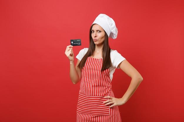 주부 여성 요리사는 붉은 벽 배경에 격리된 줄무늬 앞치마 흰색 티셔츠 토크 요리사 모자를 쓰고 제빵사를 요리합니다. 혼란스러운 여자는 신용 은행 카드 현금 없는 돈을 손에 들고 있습니다. 복사 공간 개념을 모의