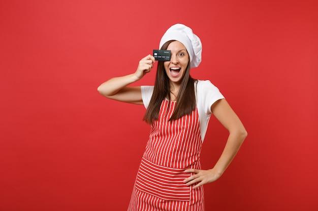 주부 여성 요리사는 붉은 벽 배경에 격리된 줄무늬 앞치마 흰색 티셔츠 토크 요리사 모자를 쓰고 제빵사를 요리합니다. 흥분한 여자는 눈을 감고 신용 은행 카드, 현금 없는 돈. 복사 공간 개념을 비웃습니다.