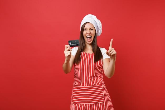 주부 여성 요리사는 붉은 벽 배경에 격리된 줄무늬 앞치마 흰색 티셔츠 토크 요리사 모자를 쓰고 제빵사를 요리합니다. 흥분된 여자는 신용 은행 카드, 현금 없는 돈을 손에 들고 있습니다. 복사 공간 개념을 모의