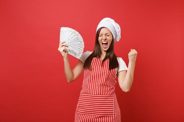 Пекарь повара повара домохозяйки женский в полосатом фартуке белой футболке toque повара шляпе изолированной на красной предпосылке стены. возбужденная женщина, держащая много долларов наличных денег банкнот. копируйте концепцию пространства копии.