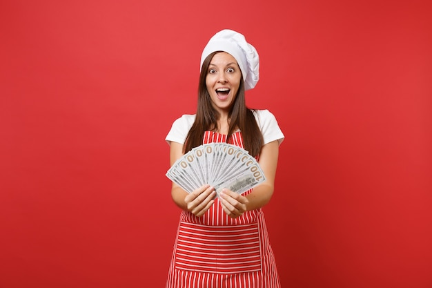 Пекарь повара повара домохозяйки женский в полосатом фартуке, белой футболке, шляпе шеф-повара toque изолированной на красной предпосылке стены. счастливая женщина, держащая много долларов наличных денег банкнот. копируйте концепцию пространства копии.