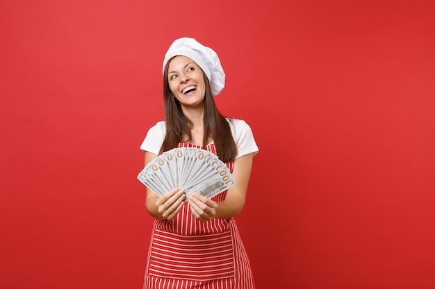 縞模様のエプロン、白いtシャツ、赤い壁の背景に分離されたトーク帽のシェフの帽子の主婦女性シェフ料理パン屋。たくさんのドル紙幣の現金を持っている幸せな女性。コピースペースの概念をモックアップします。