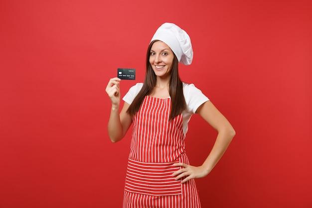주부 여성 요리사는 붉은 벽 배경에 격리된 줄무늬 앞치마 흰색 티셔츠 토크 요리사 모자를 쓰고 제빵사를 요리합니다. 웃는 여자 손에 신용 은행 카드, 현금 없는 돈을 잡으십시오. 복사 공간 개념을 모의
