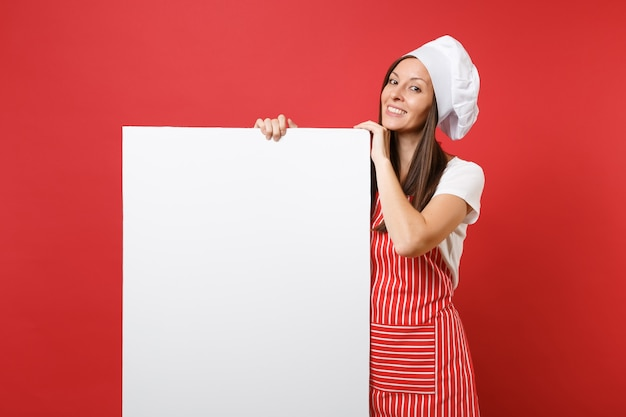 Housewife female chef cook baker in striped apron, white t-shirt, toque chefs hat isolated on red background. woman hold big white blank billboard for promotional content. mock up copy space concept.