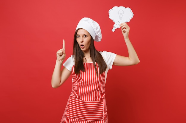 Housewife female chef cook or baker in striped apron white t-shirt toque chefs hat isolated on red wall background. confident serious woman hold say cloud lightbulb idea. mock up copy space concept.