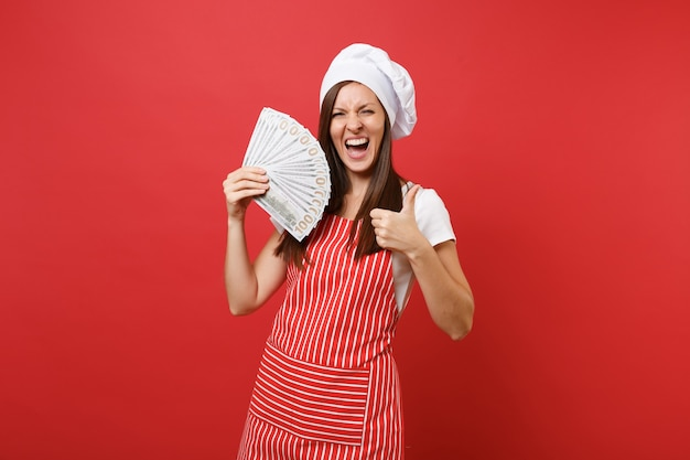 Housewife female chef cook baker in striped apron white t-shirt toque chefs hat isolated on red wall background. excited woman holding lots of dollars banknotes cash money. mock up copy space concept.