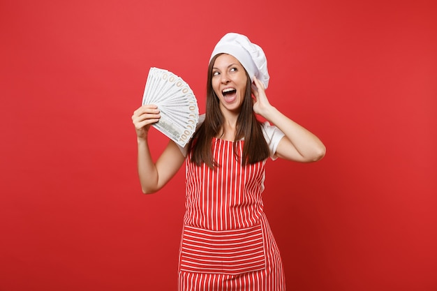 Housewife female chef cook baker in striped apron, white t-shirt, toque chefs hat isolated on red wall background. happy woman holding lots of dollars banknotes cash money. mock up copy space concept.