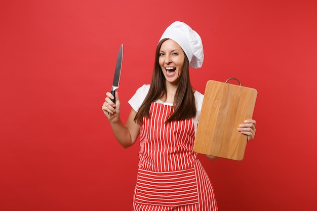 Housewife female chef cook or baker in striped apron, white t-shirt, toque chefs hat isolated on red wall background. housekeeper woman holding wooden cutting board, knife. mock up copy space concept.