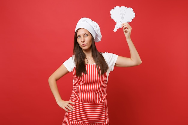 Housewife female chef cook or baker in striped apron white t-shirt toque chefs hat isolated on red wall background. pensive woman think, hold say cloud with lightbulb idea. mock up copy space concept.
