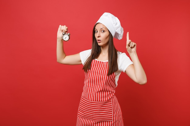 Housewife female chef cook or baker in striped apron, white t-shirt, toque chefs hat isolated on red wall background. pretty woman hold in hand retro alarm clock hurry up. mock up copy space concept.