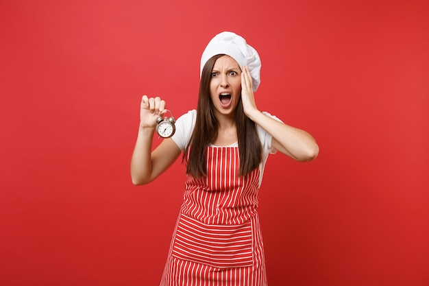 Housewife female chef cook or baker in striped apron, white t-shirt, toque chefs hat isolated on red wall background. scared woman hold in hand retro alarm clock hurry up. mock up copy space concept.