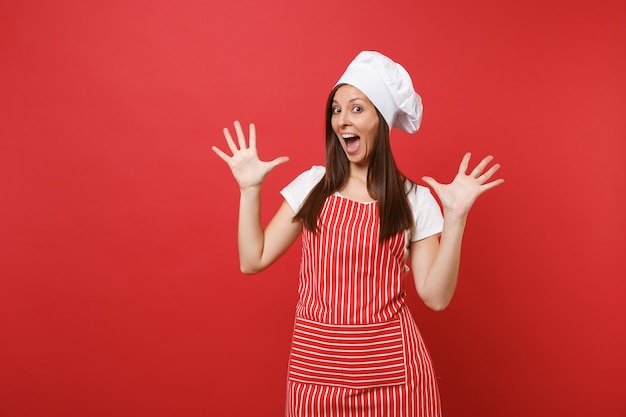 Housewife female chef cook baker in striped apron, white t-shirt, toque chefs hat isolated on red wall background. shocked mad crazy fun housekeeper woman spreading hands. mock up copy space concept.