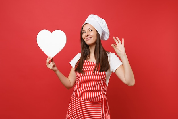 Housewife female chef cook or baker in striped apron, white t-shirt, toque chefs hat isolated on red wall background. smiling housekeeper woman hold blank heart workspace. mock up copy space concept.