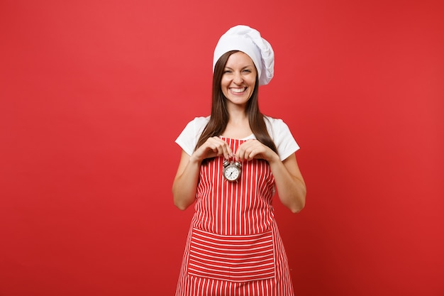 Housewife female chef cook or baker in striped apron, white t-shirt, toque chefs hat isolated on red wall background. smiling woman hold in hand retro alarm clock hurry up. mock up copy space concept.