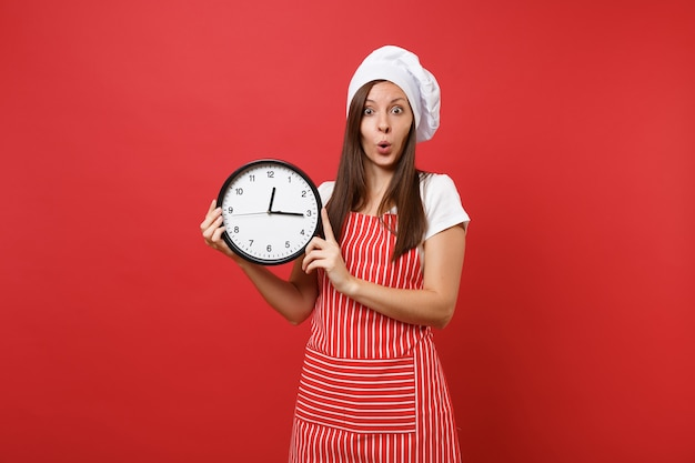 Housewife female chef cook or baker in striped apron, white t-shirt, toque chefs hat isolated on red wall background. surprised woman holding in hand round clock hurry up. mock up copy space concept.