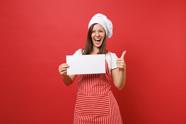 Housewife female chef cook or baker in striped apron white t-shirt toque chefs hat isolated on red wall background. woman hold blank sign board, place for promotional text. mock up copy space concept.