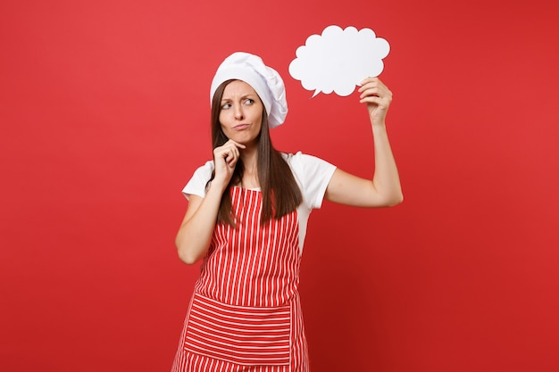 Housewife female chef cook or baker in striped apron white t-shirt toque chefs hat isolated on red wall background. woman hold in hand empty blank say cloud, speech bubble. mock up copy space concept.