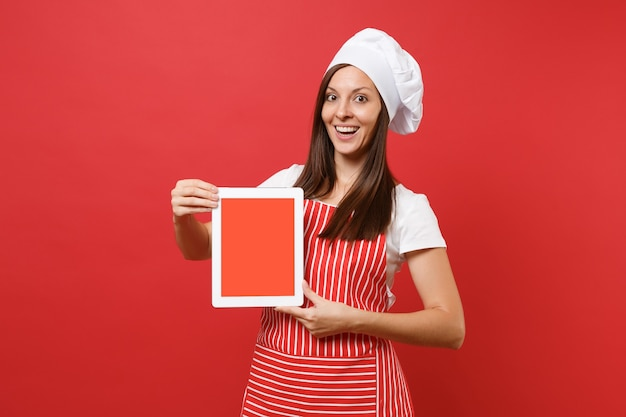 Housewife female chef cook or baker in striped apron white t-shirt toque chefs hat isolated on red wall background. woman hold tablet pc blank screen for promotional content mock up copy space concept