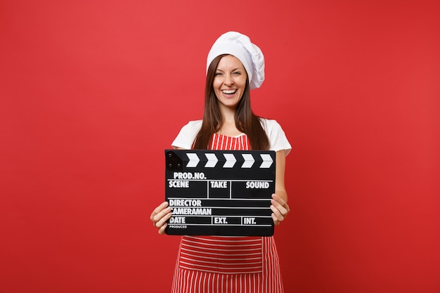 Housewife female chef cook or baker in striped apron, white t-shirt, toque chefs hat isolated on red wall background. woman holding classic black film making clapperboard. mock up copy space concept.