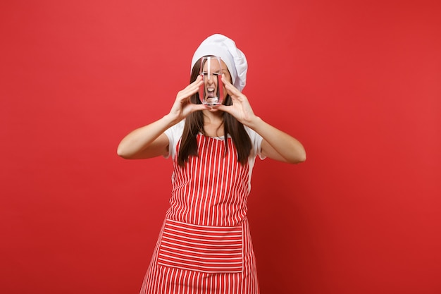 Housewife female chef cook or baker in striped apron white t-shirt toque chefs hat isolated on red wall background. woman holding drinking clear fresh pure water from glass. mock up copy space concept