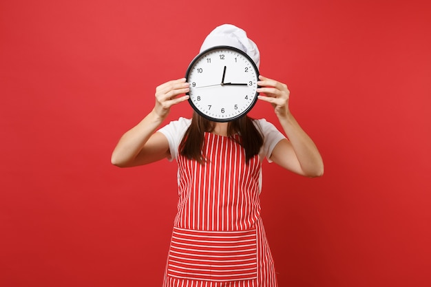 Housewife female chef cook or baker in striped apron white t-shirt toque chefs hat isolated on red wall background. woman holding in hand in front face round clock hurry up. mock up copy space concept