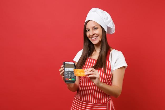 Повар шеф-повара домохозяйки женского пола или пекарь в полосатой шляпе повара toque футболки фартука изолированной на красной предпосылке стены. женщина держит в руке банковский платежный терминал, кредитная карта, устройство nfc, макет концепции копировального пространства