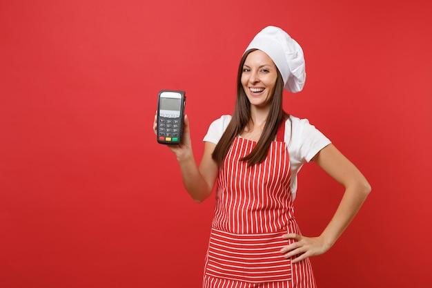 Повар шеф-повара домохозяйки женского пола или пекарь в полосатой шляпе повара toque футболки фартука изолированной на красной предпосылке стены. женщина держать в руке беспроводной банковский платежный терминал устройство nfc. копируйте концепцию пространства копии.