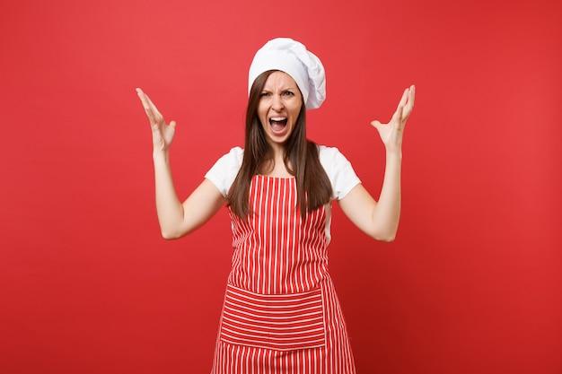 Повар шеф-повара домохозяйки или пекарь в полосатом фартуке, белой футболке, шляпе шеф-повара toque изолированной на красной предпосылке стены. злой сумасшедший шокирован женщина-экономка, разводя руками. копируйте концепцию пространства копии.