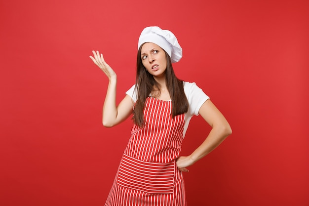 縞模様のエプロン、白いtシャツ、赤い壁の背景に分離されたトーク帽のシェフの帽子の主婦女性シェフ料理人またはパン屋。魅力的な悲しい動揺家政婦の女性が手を上げた。コピースペースの概念をモックアップします。