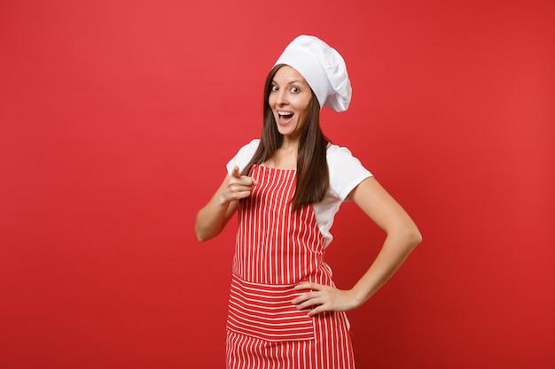 Повар шеф-повара домохозяйки или пекарь в полосатом фартуке, белой футболке, шляпе шеф-повара toque изолированной на красной предпосылке стены. красивая женщина экономки указывая пальцем на камеру. копируйте концепцию пространства копии.