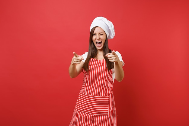 縞模様のエプロン、白いtシャツ、赤い壁の背景に分離されたトーク帽のシェフの帽子の主婦女性シェフ料理人またはパン屋。指カメラを指す美しい家政婦の女性。コピースペースの概念をモックアップします。