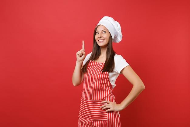 縞模様のエプロン、白いtシャツ、赤い壁の背景に分離されたトーク帽のシェフの帽子の主婦女性シェフ料理人またはパン屋。人差し指を上に向ける美しい家政婦の女性。コピースペースの概念をモックアップします。