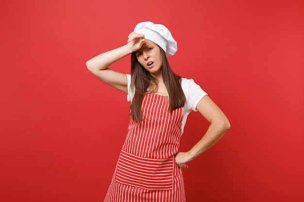 縞模様のエプロン、白いtシャツ、赤い壁の背景に分離されたトーク帽のシェフの帽子の主婦女性シェフ料理人またはパン屋。美しい家政婦の女性は頭の額に手を置きます。コピースペースの概念をモックアップします。