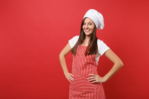 縞模様のエプロン、白いtシャツ、赤い壁の背景に分離されたトーク帽のシェフの帽子の主婦女性シェフ料理人またはパン屋。腕を腰に当てて立っている美しい家政婦の女性。コピースペースの概念をモックアップします。