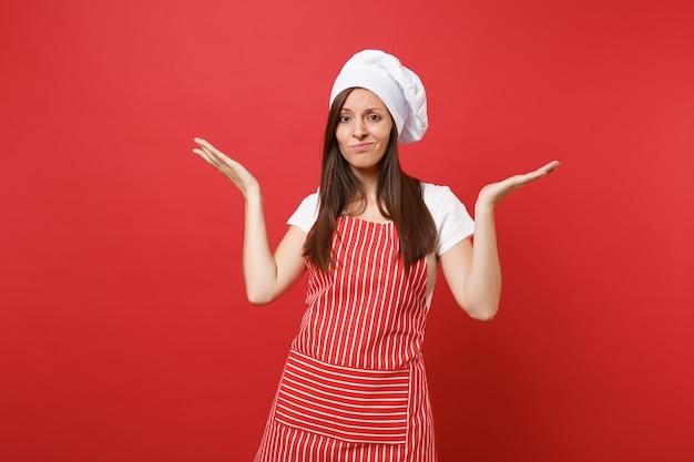 縞模様のエプロン、白いtシャツ、赤い壁の背景に分離されたトーク帽のシェフの帽子の主婦女性シェフ料理人またはパン屋。手を広げている美しい当惑した家政婦の女性。コピースペースの概念をモックアップします。