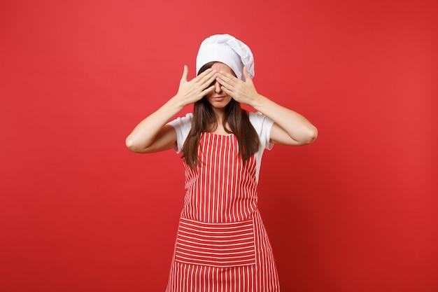 縞模様のエプロン、白いtシャツ、赤い壁の背景に分離されたトーク帽のシェフの帽子の主婦女性シェフ料理人またはパン屋。美しい悲しい動揺家政婦の女性は目に手を置いた。コピースペースの概念をモックアップ