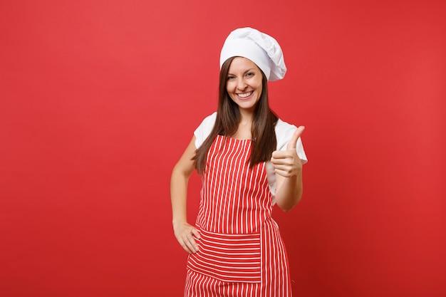 縞模様のエプロン、白いtシャツ、赤い壁の背景に分離されたトーク帽のシェフの帽子の主婦女性シェフ料理人またはパン屋。親指を立てて見せてくれる美しい笑顔の家政婦。コピースペースの概念をモックアップします。