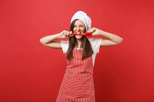 縞模様のエプロン、白いtシャツ、赤い壁の背景に分離されたトーク帽のシェフの帽子の主婦女性シェフ料理人またはパン屋。お皿を洗うために口のブラシで保持する楽しい狂った女性。コピースペースの概念をモックアップ