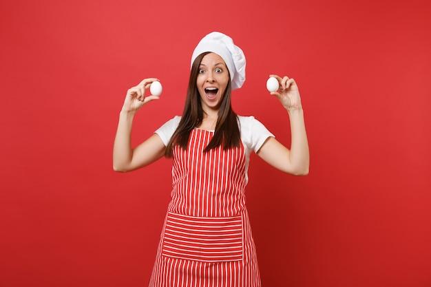 주부 여성 셰프는 줄무늬 앞치마, 흰색 티셔츠, 빨간 벽 배경에 격리된 토크 셰프 모자를 쓰고 제빵사를 요리합니다. 재미있는 가정부 여자는 두 개의 닭고기 달걀을 손에 쥐고 있습니다. 복사 공간 개념을 비웃습니다.