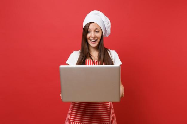 주부 여성 셰프는 줄무늬 앞치마, 흰색 티셔츠, 빨간 벽 배경에 격리된 토크 셰프 모자를 쓰고 제빵사를 요리합니다. 노트북 pc에서 레시피를 찾는 재미있는 가정부 여자. 복사 공간 개념을 비웃습니다.