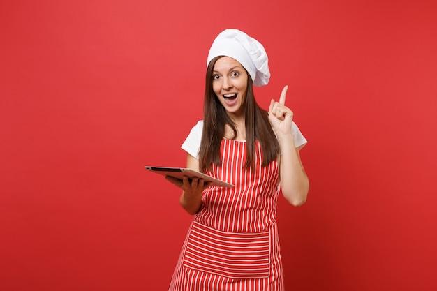 주부 여성 셰프는 줄무늬 앞치마, 흰색 티셔츠, 빨간 벽 배경에 격리된 토크 셰프 모자를 쓰고 제빵사를 요리합니다. 태블릿 pc에서 레시피를 찾는 재미있는 가정부 여자. 복사 공간 개념을 비웃습니다.