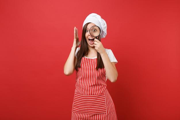붉은 벽 배경에 격리된 줄무늬 앞치마 흰색 티셔츠 토크 셰프 모자를 쓴 주부 여성 요리사 또는 제빵사. 가정부 여자 잡고 돋보기를 통해 봐. 복사 공간 개념을 모의