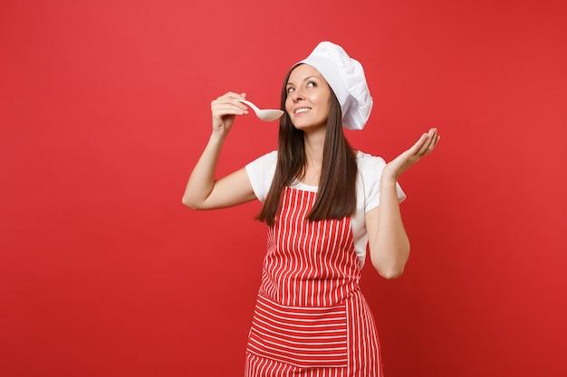 縞模様のエプロン、白いtシャツ、赤い壁の背景に分離されたトーク帽のシェフの帽子の主婦女性シェフ料理人またはパン屋。ハウスキーパーの女性がおたまひしゃくで試飲。コピースペースの概念をモックアップします。
