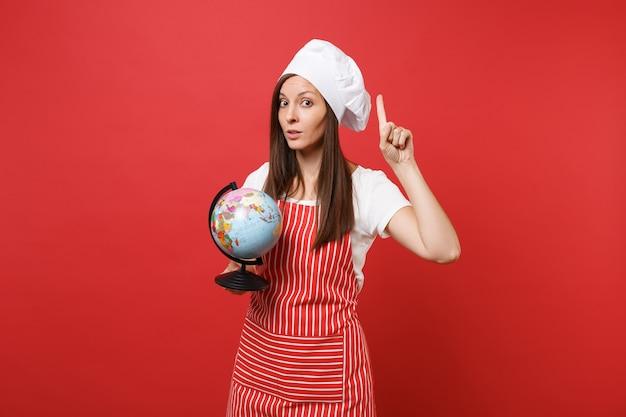 Повар шеф-повара домохозяйки или пекарь в полосатом фартуке, белой футболке, шляпе шеф-повара toque изолированной на красной предпосылке стены. домработница женщина, держащая в ладонях глобус мира земли. копируйте концепцию пространства копии.