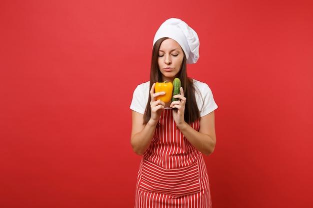 縞模様のエプロン、白いtシャツ、スタジオの赤い壁の背景に分離されたトーク帽のシェフの帽子の主婦女性シェフ料理人またはパン屋。女性は黄色いコショウ、緑のキュウリを保持します。コピースペースの概念をモックアップします。
