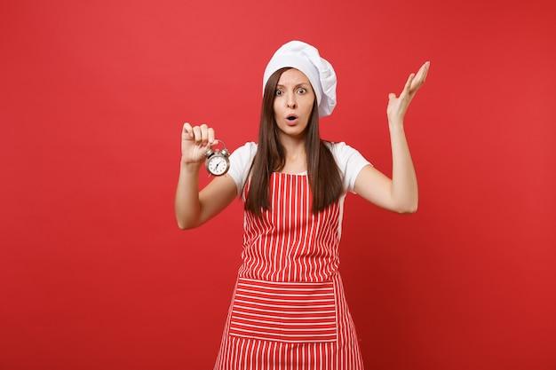 Повар шеф-повара домохозяйки или пекарь в полосатом фартуке, белой футболке, шляпе шеф-повара toque изолированной на красной предпосылке стены. потрясенная женщина держит в руке ретро-будильник, торопитесь. копируйте концепцию пространства копии.
