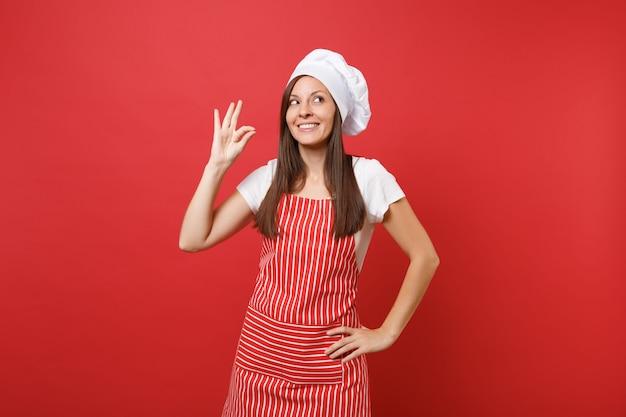 縞模様のエプロンの白いtシャツ、赤い壁の背景に分離されたトーク帽のシェフの帽子の主婦の女性シェフの料理人またはパン屋。大丈夫味の喜びのサインを作る笑顔の穏やかなかわいい女性。コピースペースの概念をモックアップします。
